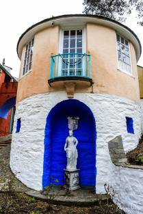 A curved building with a balcony and statue at Portmeirion Village