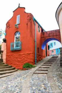 A cobbled street passing through an archway of a brightly coloured building in Portmeirion Village